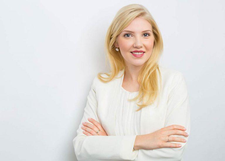 Bewerbungsfotos Berlin - Modernes Bewerbungsfoto einer Frau mit verschränkten Armen und langen, blonden Haaren vor weißem Hintergrund vom Fotostudio Farbtonwerk in Berlin Mitte