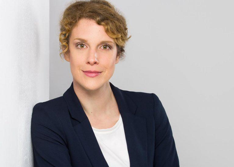 Bewerbungsfotos Berlin -Modernes Bewerbungsfoto einer Frau mit hellbraunen Lockenfrisur, die einen dunkelblauen Blazer mit weißem Shirt kombiniert trägt vom Fotostudio Farbtonwerk in Berlin Mitte