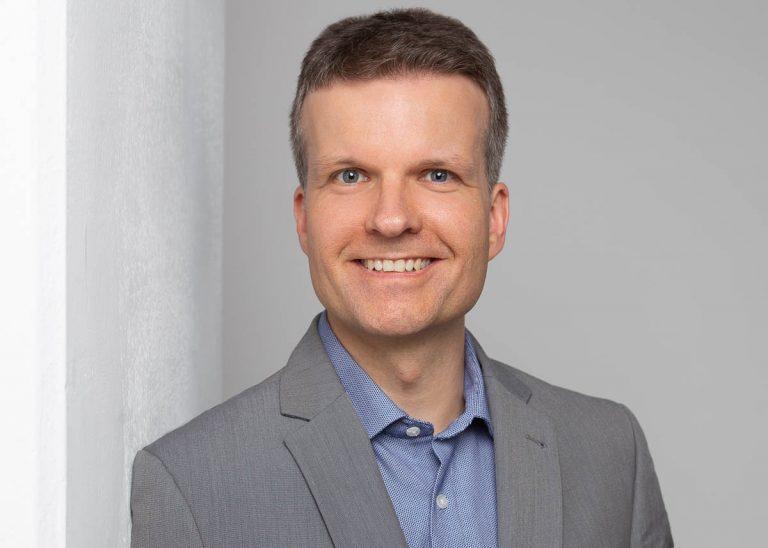 Bewerbungsfotos Berlin -Modernes Bewerbungsfoto eines Mannes, der in einem grauen Sakko und blauem Hemd vor einem hellen Hintergrund an einer Säule lehnt vom Fotostudio Farbtonwerk in Berlin Mitte