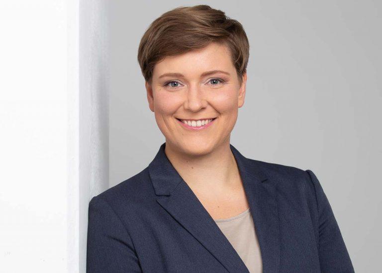 Bewerbungsfotos Berlin -Modernes Bewerbungsfoto einer Frau mit kurzen, braunen Haare und einem blauen Blazer vor einem hellen Hintergrund vom Fotostudio Farbtonwerk in Berlin Mitte