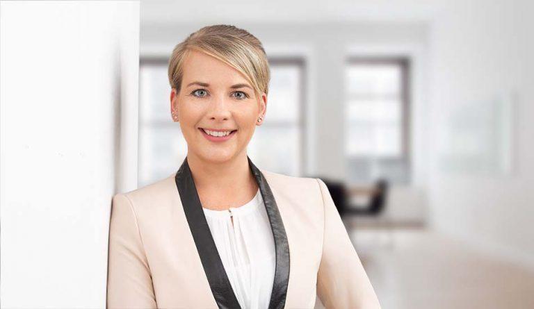 Bewerbungsfotos Berlin -Modernes Bewerbungsfoto einer Frau mit hellem Blazer, die in einem hellen Büro an der Wand gelehnt steht vom Fotostudio Farbtonwerk in Berlin Mitte