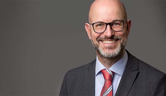 Bewerbungsfotos Berlin -Modernes Bewerbungsfoto eines freundlich lächelnden Mannes mit Brille, Vollbart und roter Krawatte vor grauem Hintergrund vom Fotostudio Farbtonwerk in Berlin Mitte