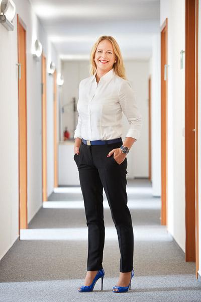 Businessportraits von Sandra Bohrisch, Geschäftsführerin des BVI Bundesfachverbandes der Immobilienverwalter. Sie steht im Flur der Büros.