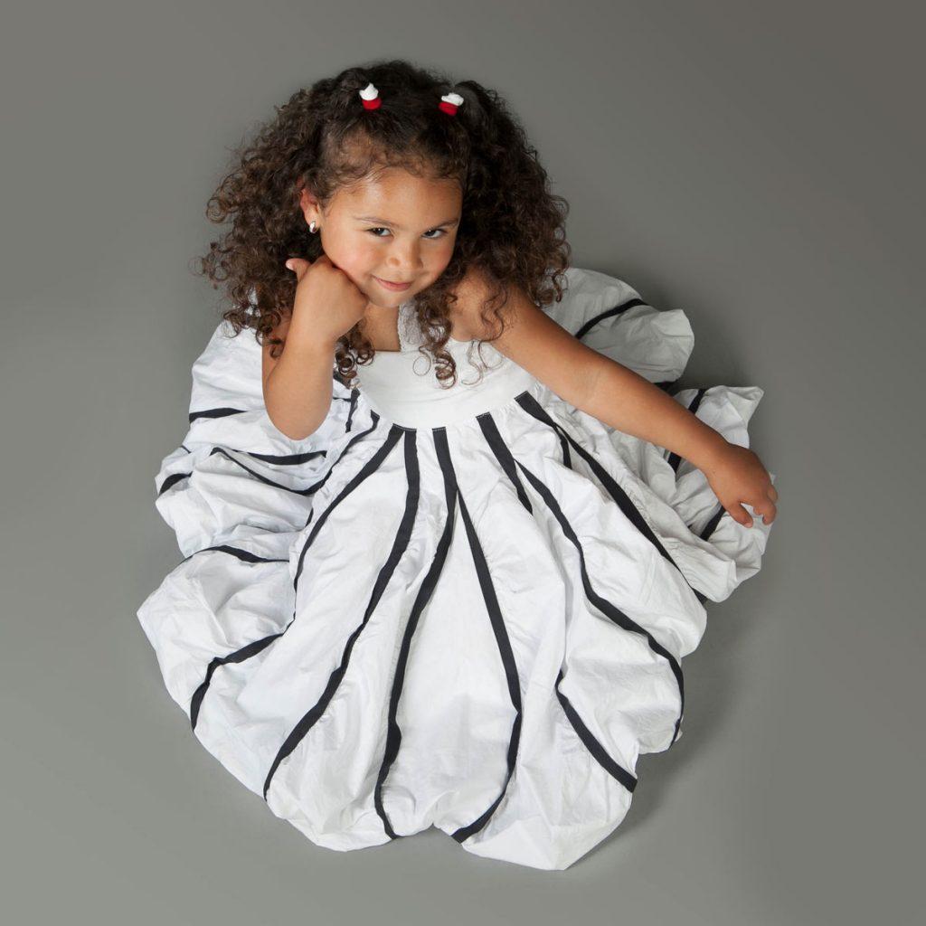 dunkelhäutiges Mädchen in weißem Kleid blickt neckisch nach oben in die Kamera