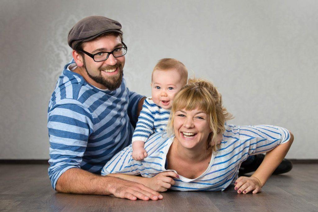 Familie mit blau gestreiften Shirts liegt lachend auf dem Boden