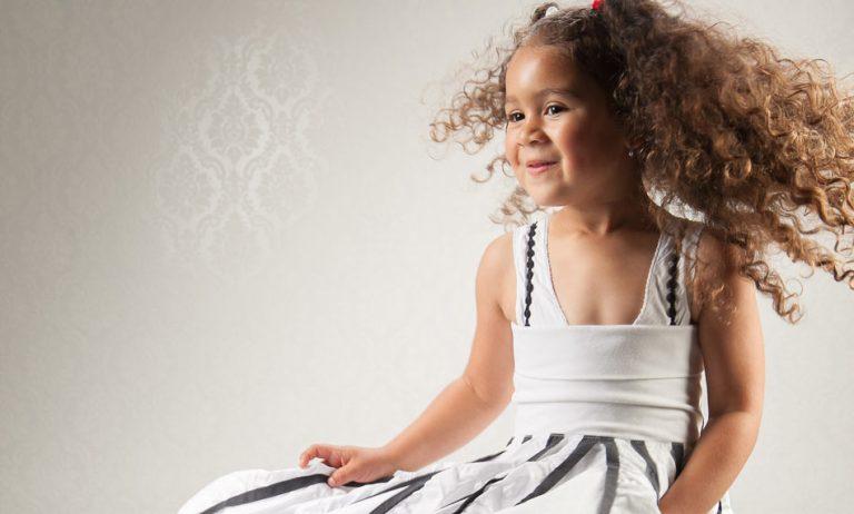 Kleines, dunkelhäutiges Mädchen tanzt in weißem Kleid