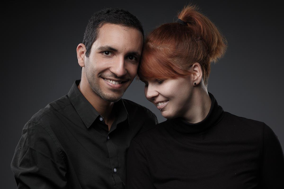 Eine junge Frau mit roten Haaren lehnt ihren Kopf liebevoll an ihren Freund, der glücklich in die Kamera lächelt