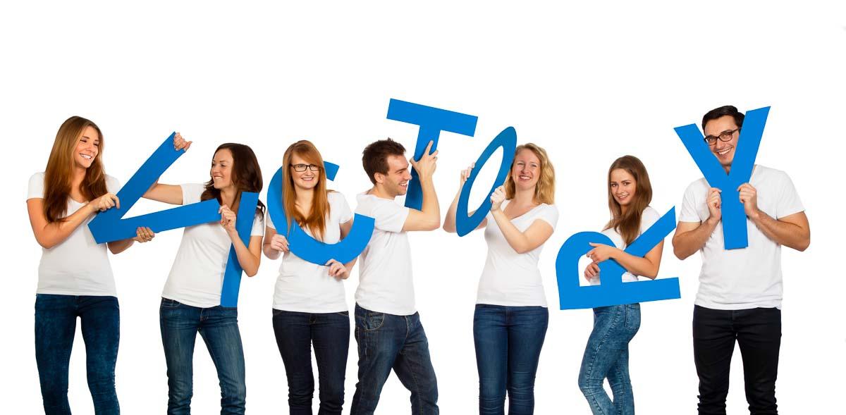 Die Hostessen vom Victory People albern mit blauen Buchstaben herum
