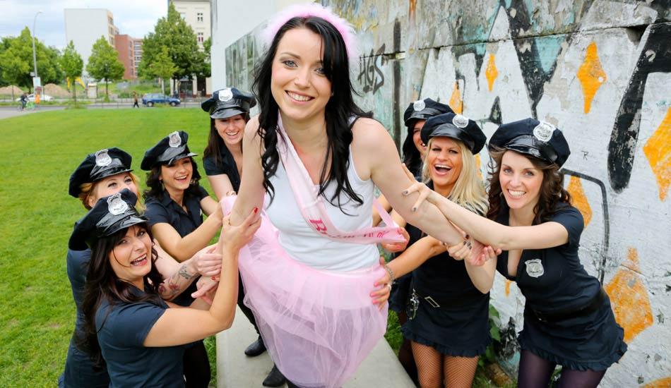Junggesellinnen in US Polizeiuniformen halten die Braut beim Outdoor JGA-Fotoshooting fest
