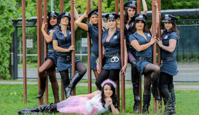 Junggesellinnen beim JGA Fotoshooting mit Sexy US Polizeiuniformen posen draußen an Stangen