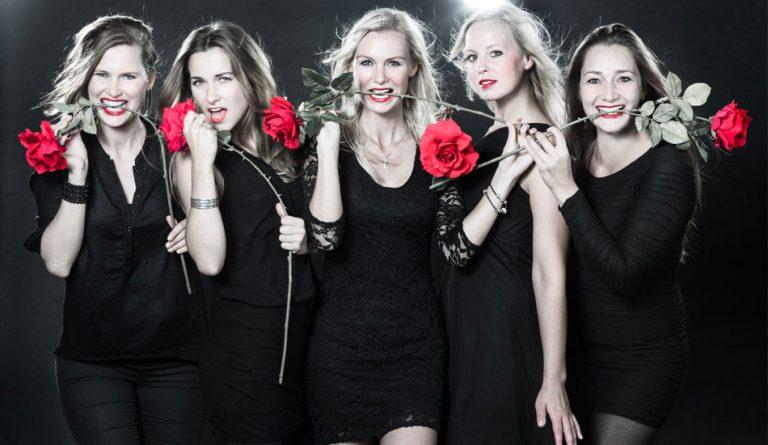 Sexy Junggesellinen beim JGA-Fotoshooting im Studio mit schwarzen Kleidern und roten Rosen im Mund