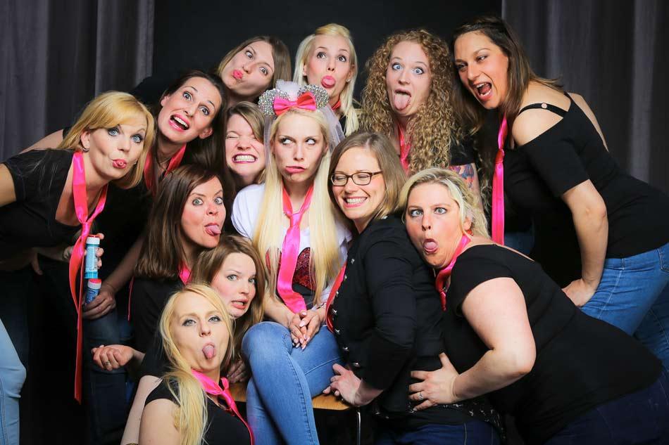 Junggesellinnen mit rosa Krawatten bilden einen Kreis um die Braut beim JGA-Fotoshooting und machen alle eine Grimasse