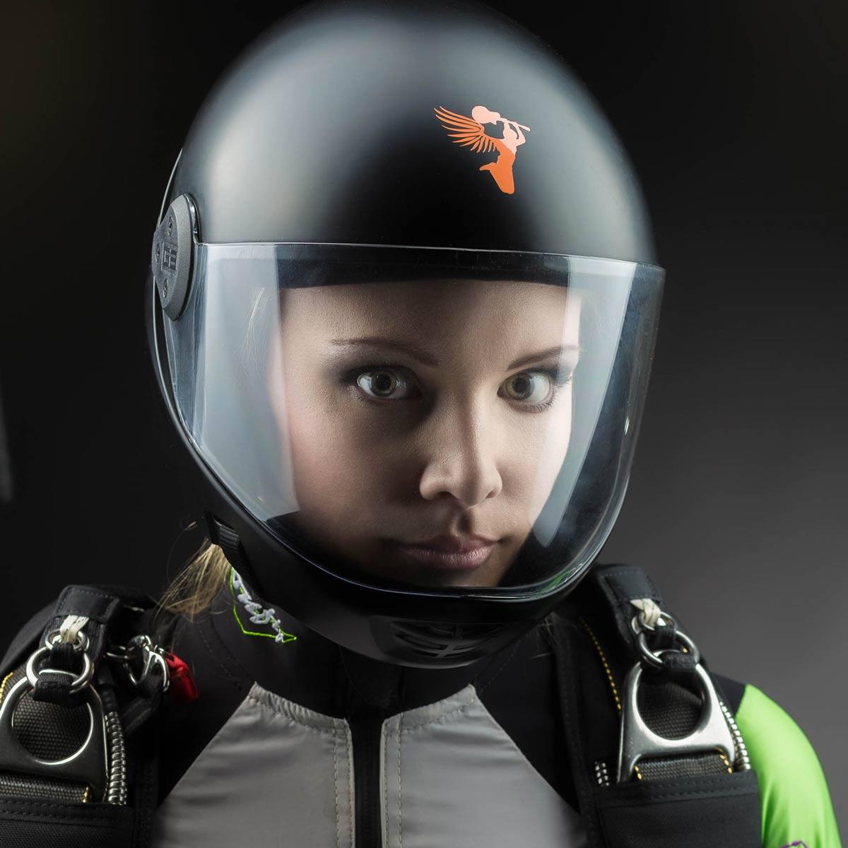 Portraitfoto einer jungen Frau mit Helm und Fallschirmspringer Outfit