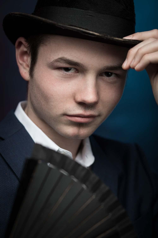 Künstler-Portraitfoto eines jungen Zauberers mit Zylinder und einem schwarzen Fächer der Hand