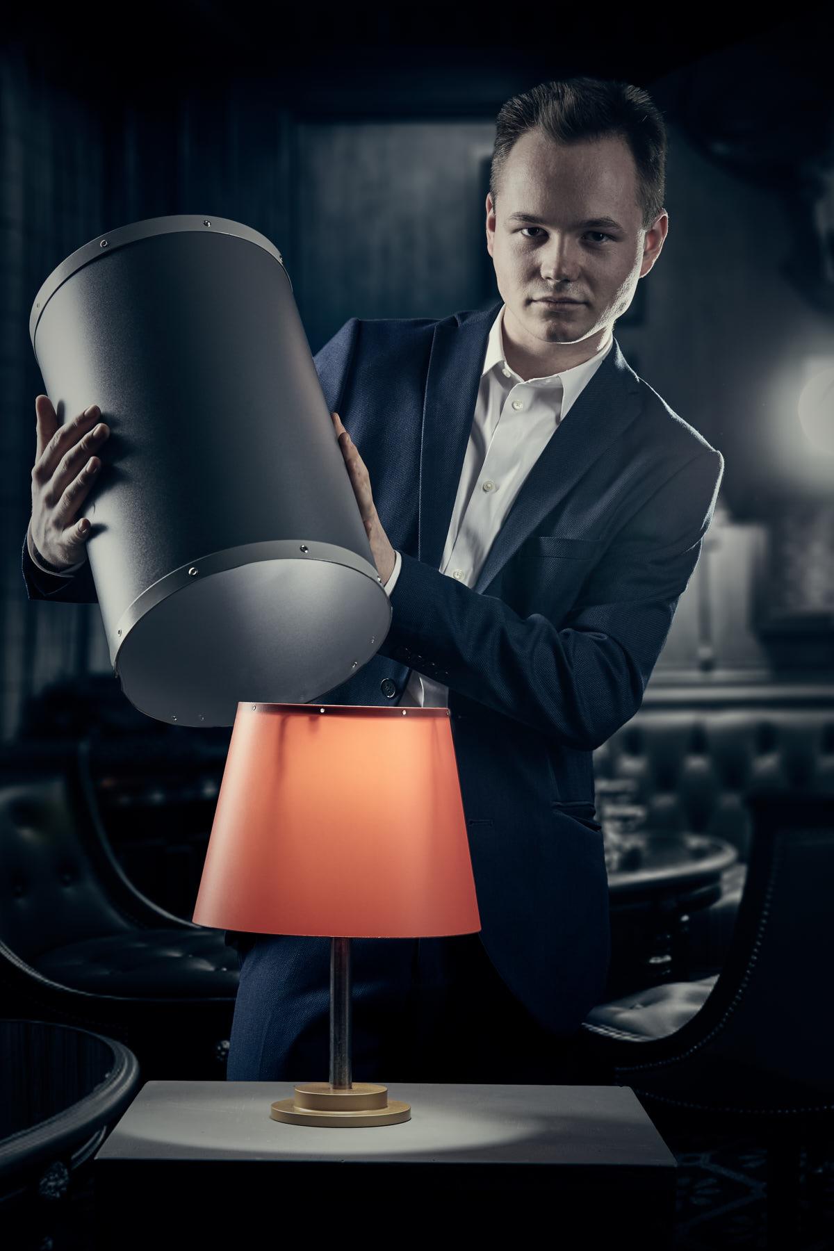 Künstlerportrait eines jungen Zauberers im Anzug der ein orangenen Lampe aus einem Rohr zaubert