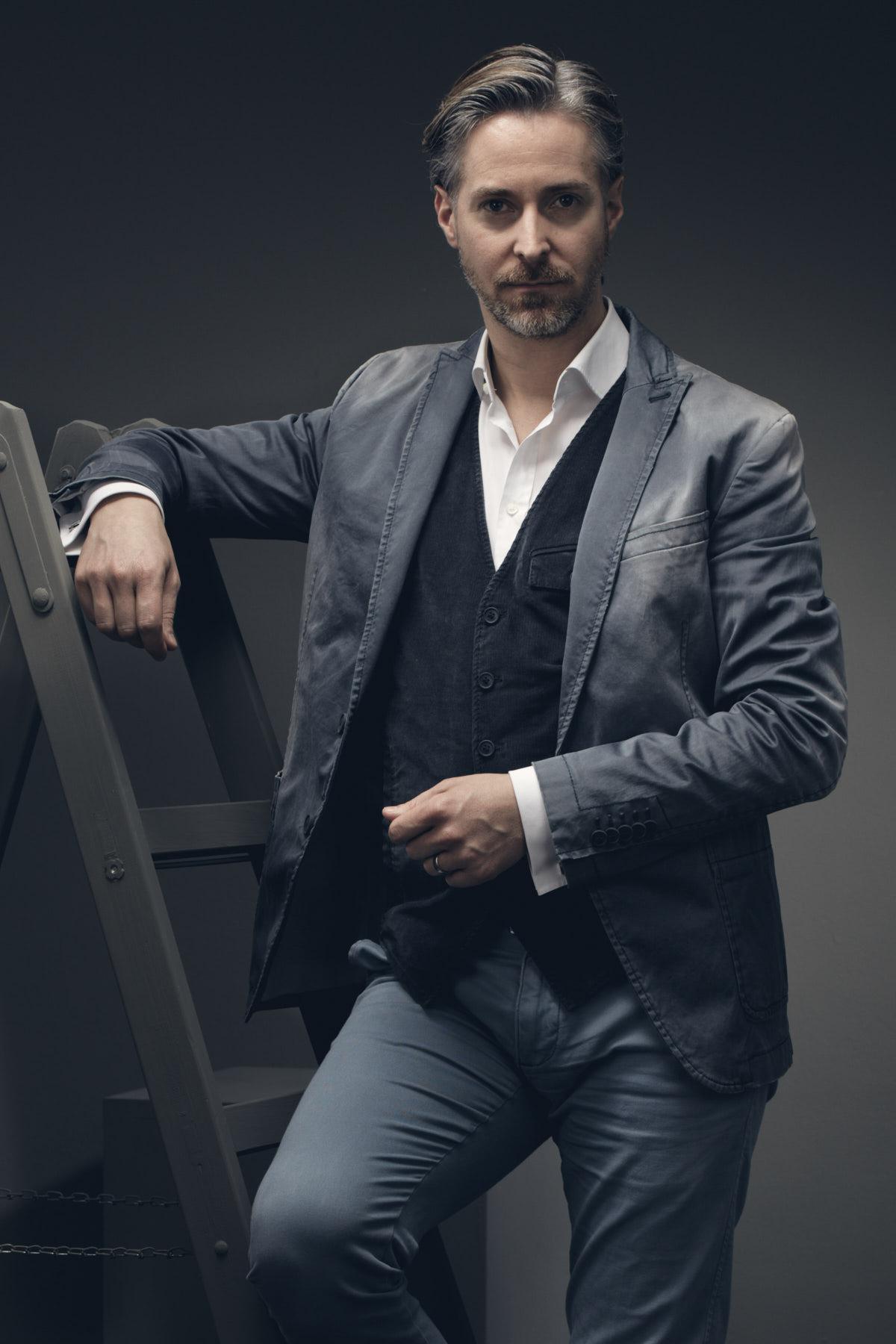 Künstlerportrait eines Schauspielers, der ein Drycorn Jacket trägt und  sich auf eine graue Leiter stützt