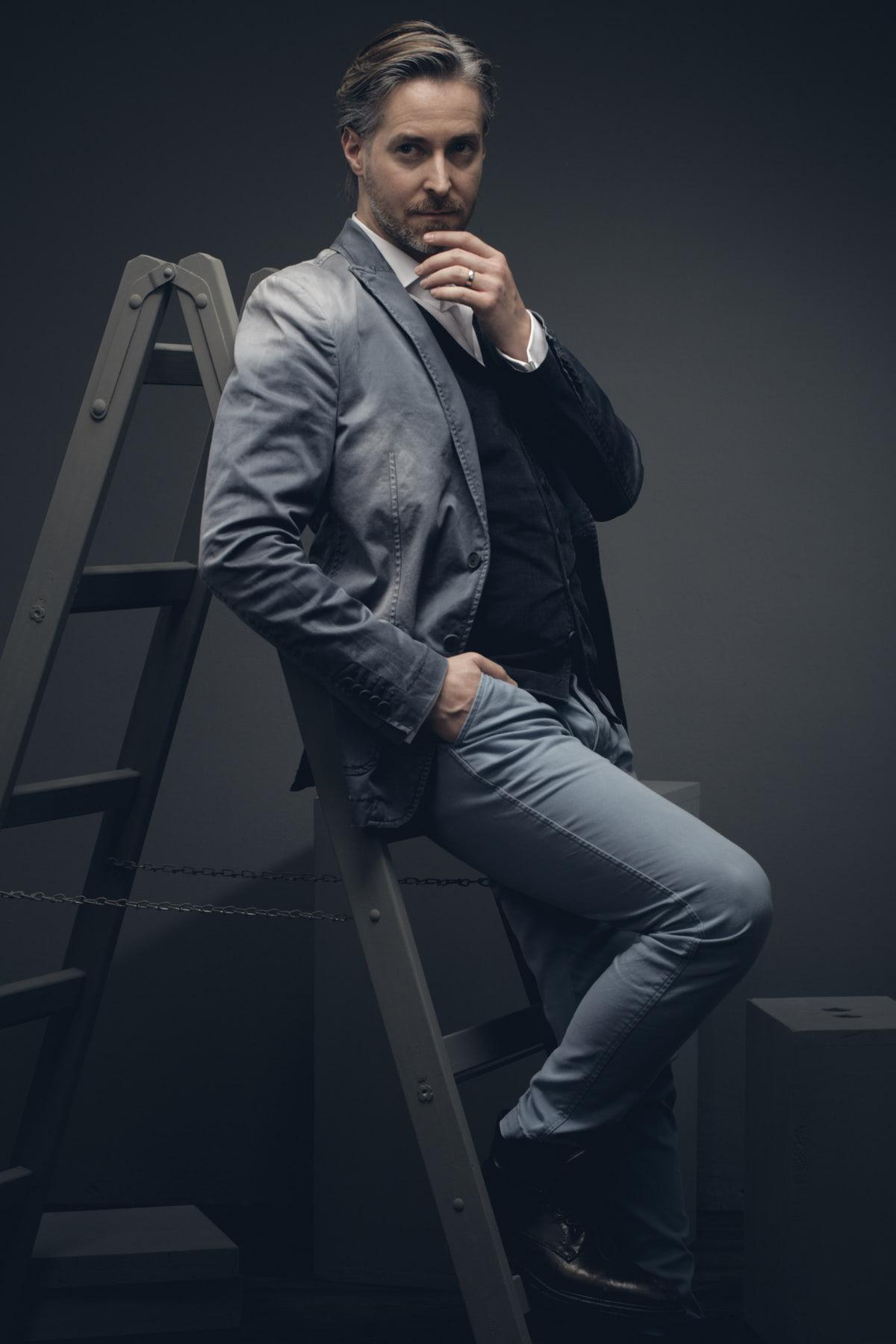 Künstlerportrait eines Schauspielers, der ein nachdenklich an einer graue Leiter lehnt
