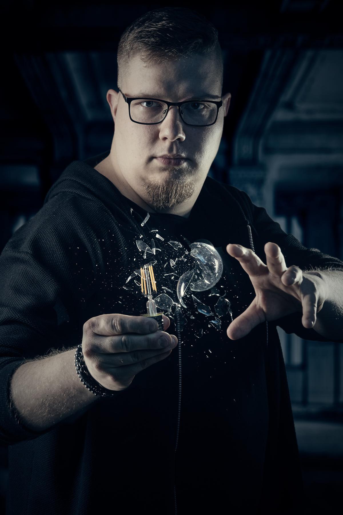 Künstlerportrait eines jungen Zauberers der eine Glühbirne zerspringen läßt