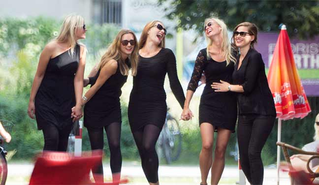 Fünf junge Frauen in schwarzen Cocktailkleidern haben Spaß bei Ihrem JGA Junggesellinnenabschied Fotoshooting.